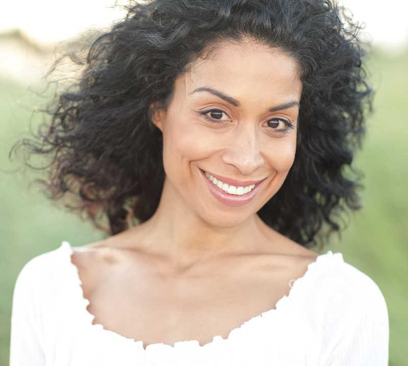 smiling woman with dark skin, white shirt | 9 of the Best Treatments for Dark Skin | Masterpiece Skin Restoration