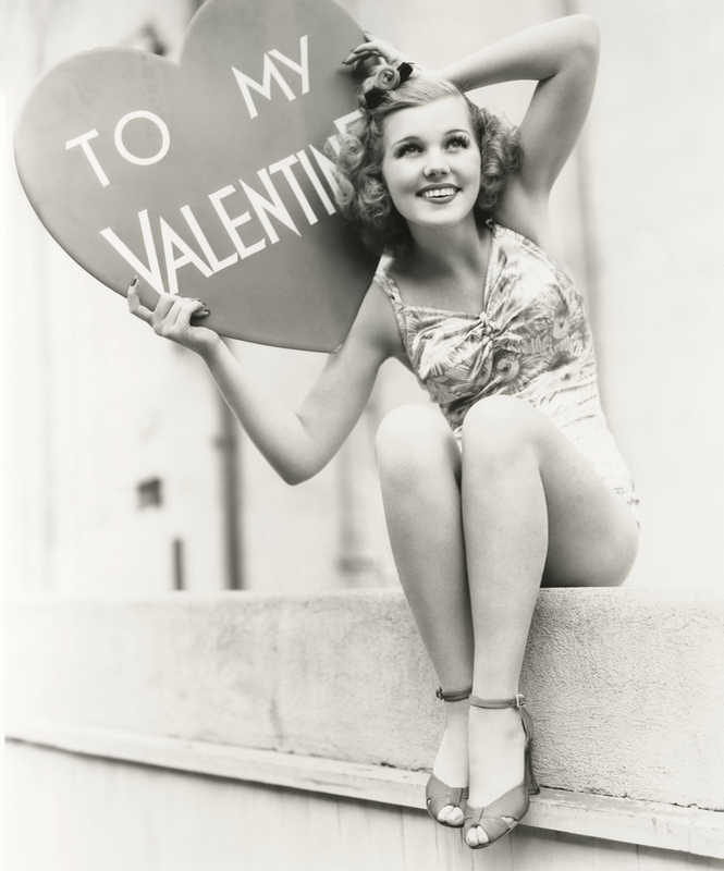 Old black and white photo of young woman in a bathing suit holding a valentine web