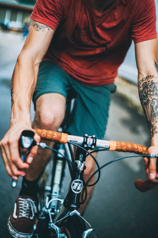 Closeup of bike rider with tattoos on his arms