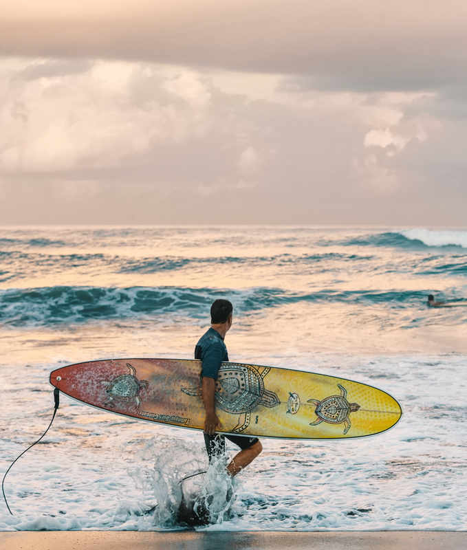 man carrying a surfboard on the beach | Wellbeing Category | Masterpiece Skin Restoration