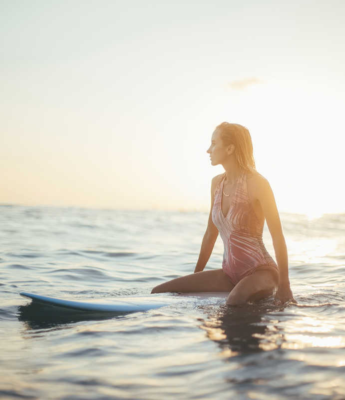 woman sitting on a surfboard in in the ocean | CoolSculpting & CoolMini for Stubborn Fat | Masterpiece Skin Restoration