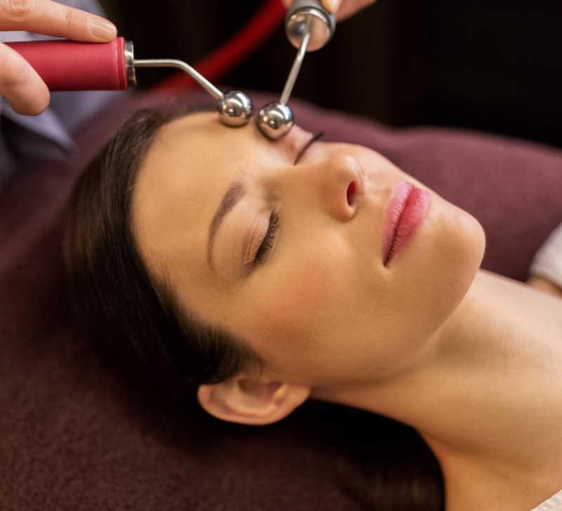 Beautiful woman with dark hair getting a microcurrent facial   Masterpiece Skin Restoration