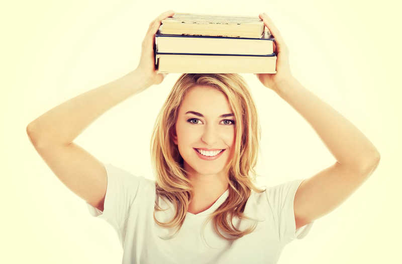 beautiful young woman smiling holding a stack of books on her head | Read Our Reviews! | Masterpiece Skin Restoration