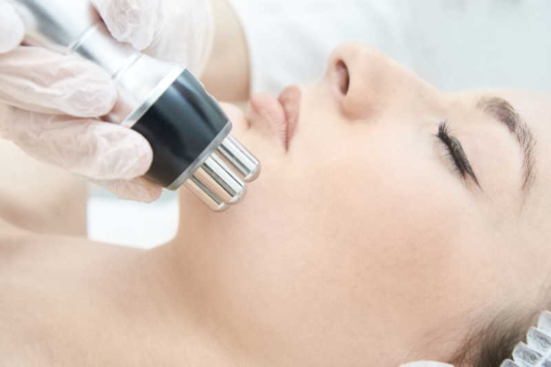 Closeup of a woman with beautiful skin getting a microcurrent facial   Masterpiece Skin Restoration