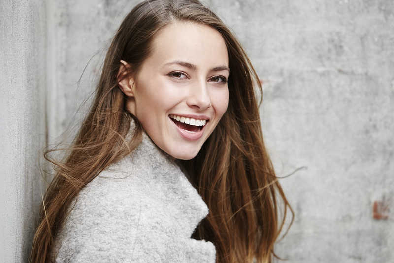pretty young woman smiling wearing a grey coat leaning against a wall | Read Our Reviews! | Masterpiece Skin Restoration
