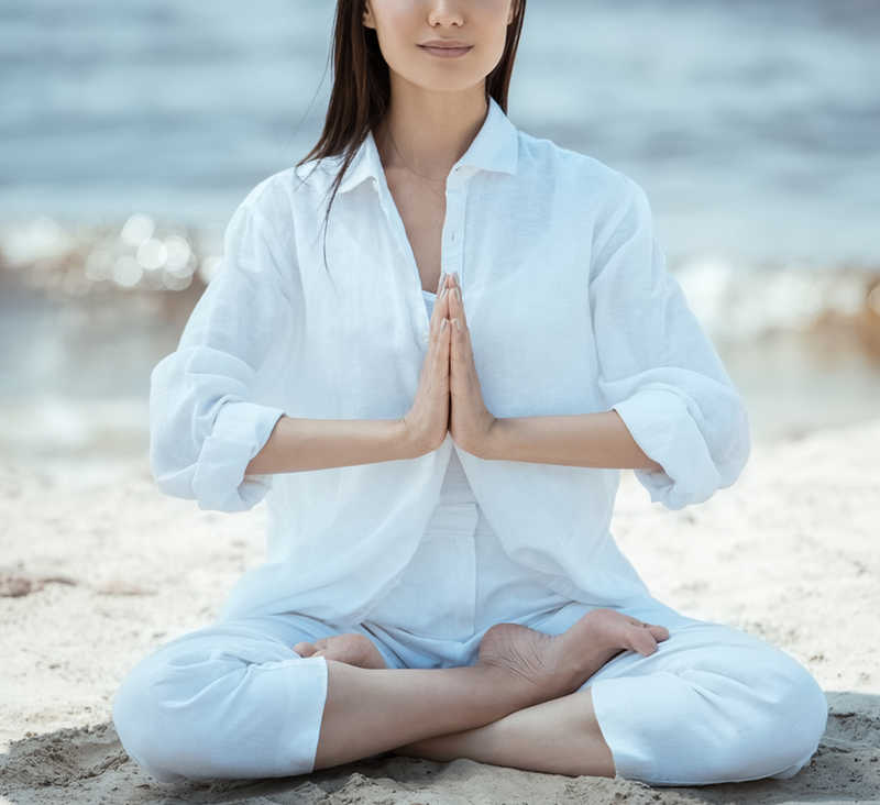 woman meditating on the beach | 8 Science-Based Health Benefits Of Meditation You Didn't Know About | Masterpiece Skin Restoration
