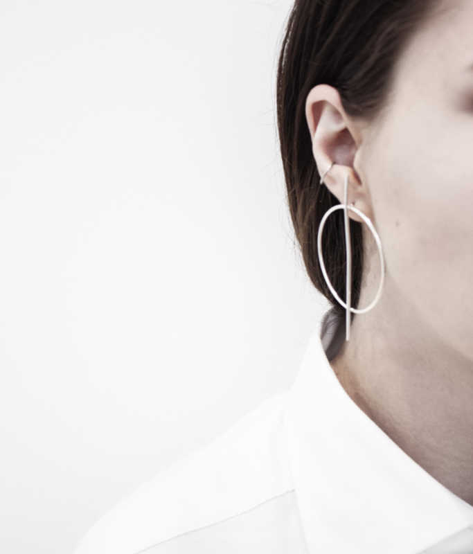Part of woman's face and 1 ear wearing earrings & white shirt on a white background.