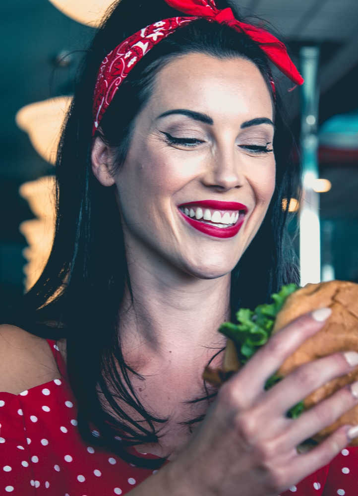 Pretty woman with red lipstick eating a hamburger