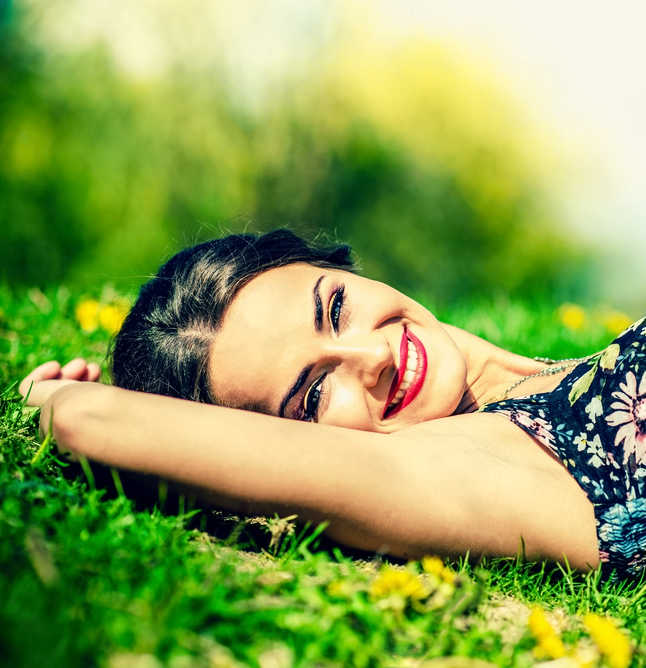 beautiful young woman wearing red lipstick, blue floral dress lying down in the grass