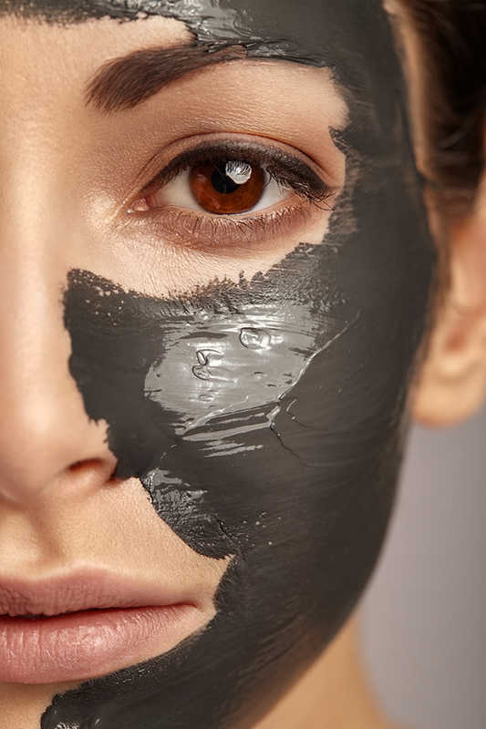 closeup of half of woman's face with dark brown facial mask