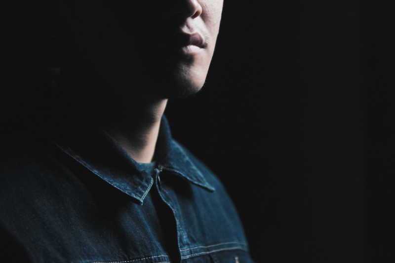 Lower half of man's face with strong chin wearing denim shirt, black background.