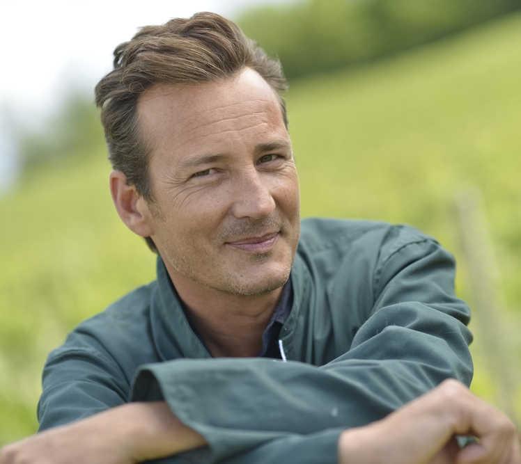mature man, brown hair, green jacket smiling