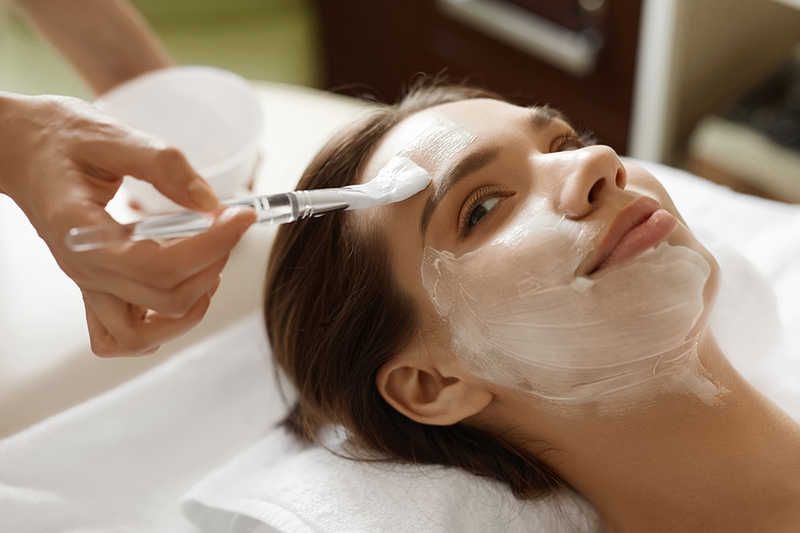 smiling woman getting a facial mask applied to her face with a brush