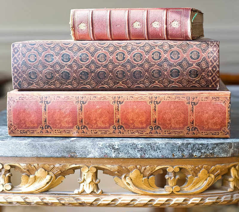 Old leatherbound books on an ornate antique library table