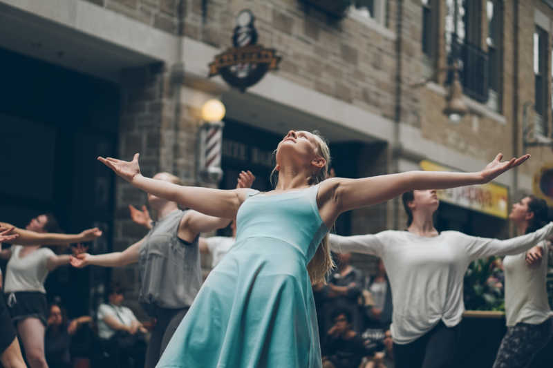 A crowd dances in the street in Guelph with their arms spread, looking upward.