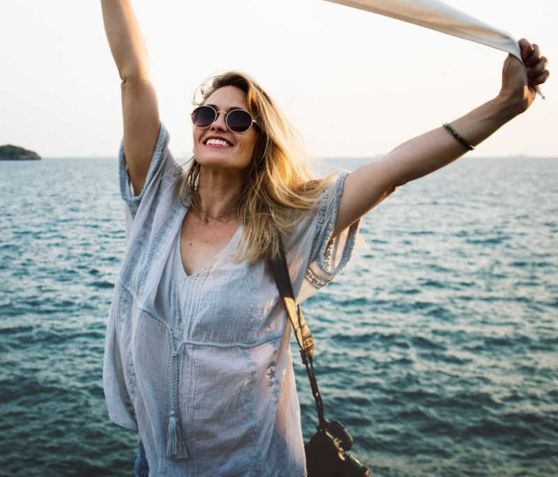 woman wearing sunglasses holding her scarf over her head, ocean background