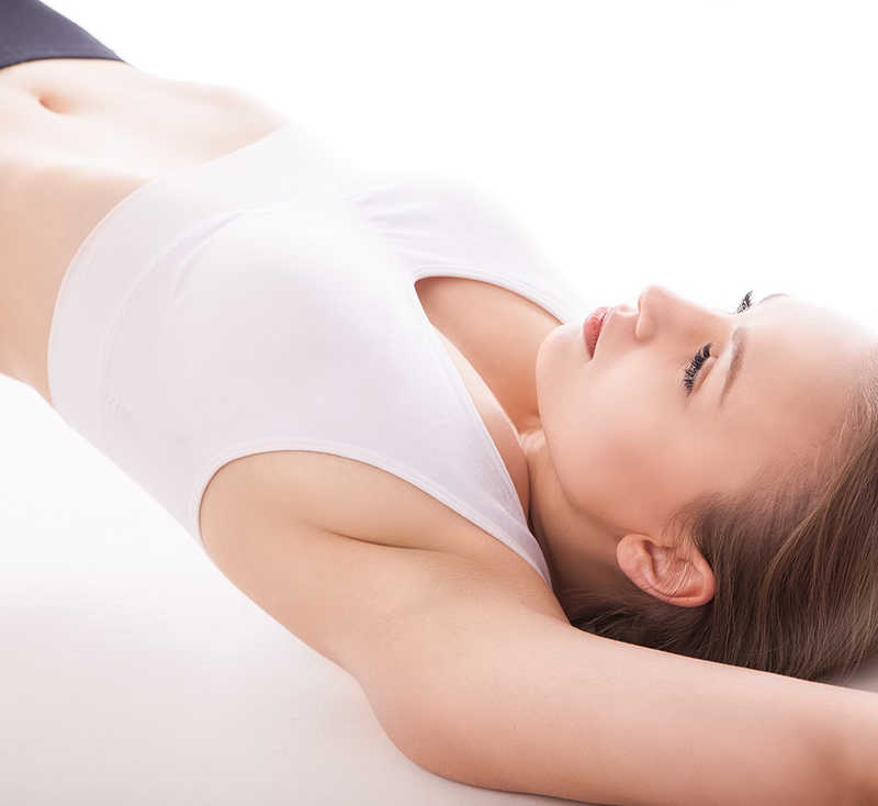 woman wearing white sports bra, abdomen exposed lying on back exercising