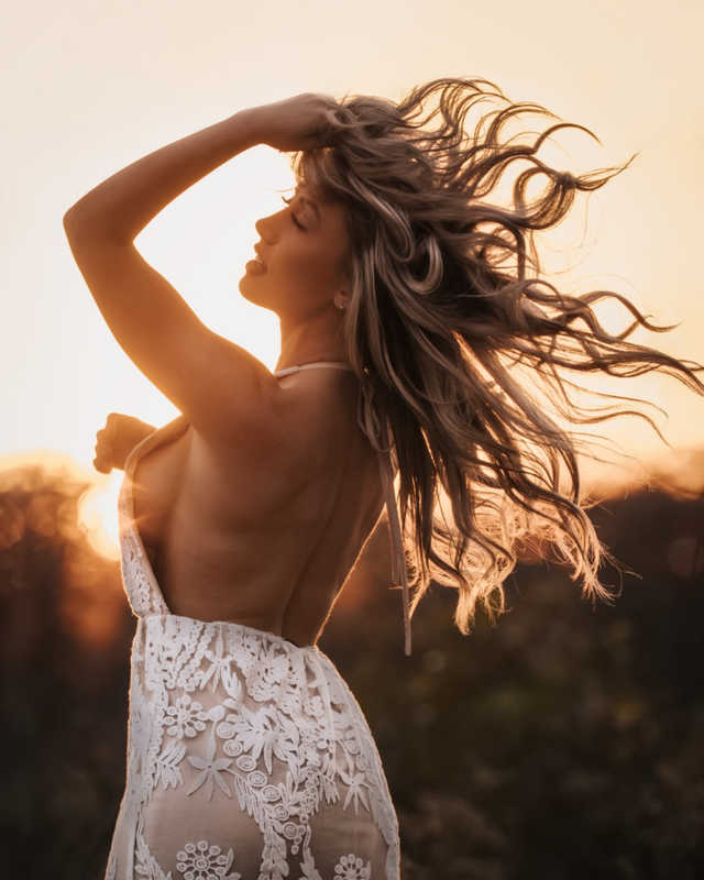Beautiful woman, hand in her long blonde hair, wearing a lace dress, standing in front of a sunset.