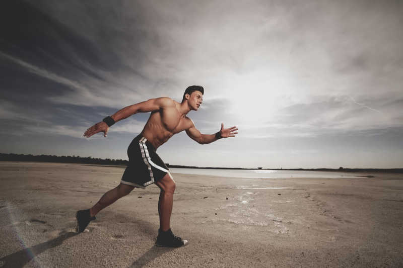 young fit man running on the beach without a shirt
