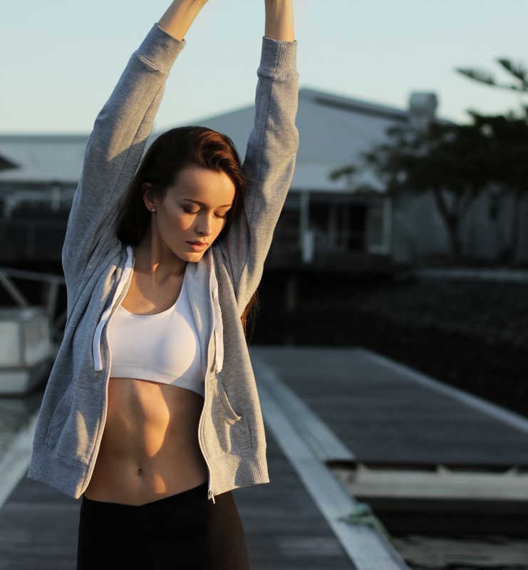 Beautiful woman with long dark hair and sports bra stretching outside
