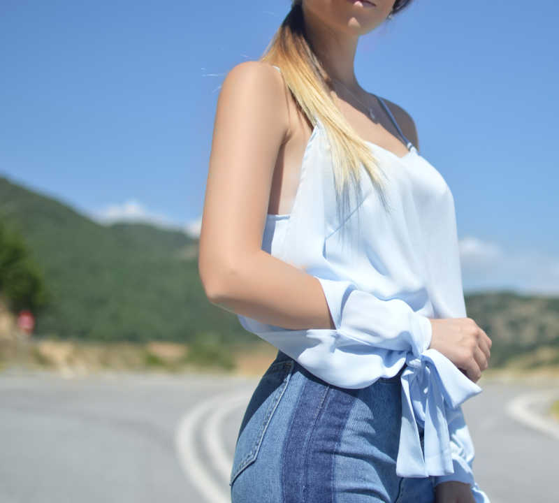 Torso of woman with great figure wearing blue blouse and jeans standing on a road.